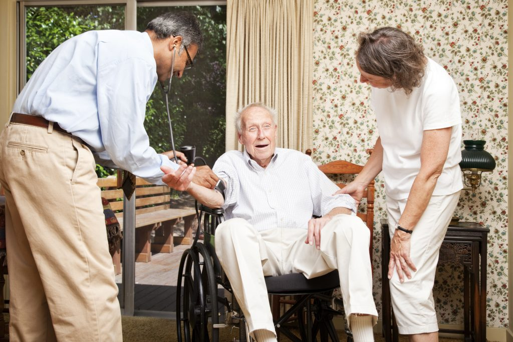 Doctor providing primary care in the home to a chronically ill patient