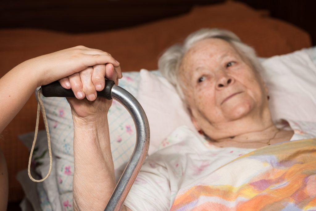 Elderly woman with walker sick in bed