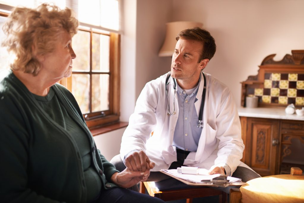 Doctor making a house call discussing serious illness