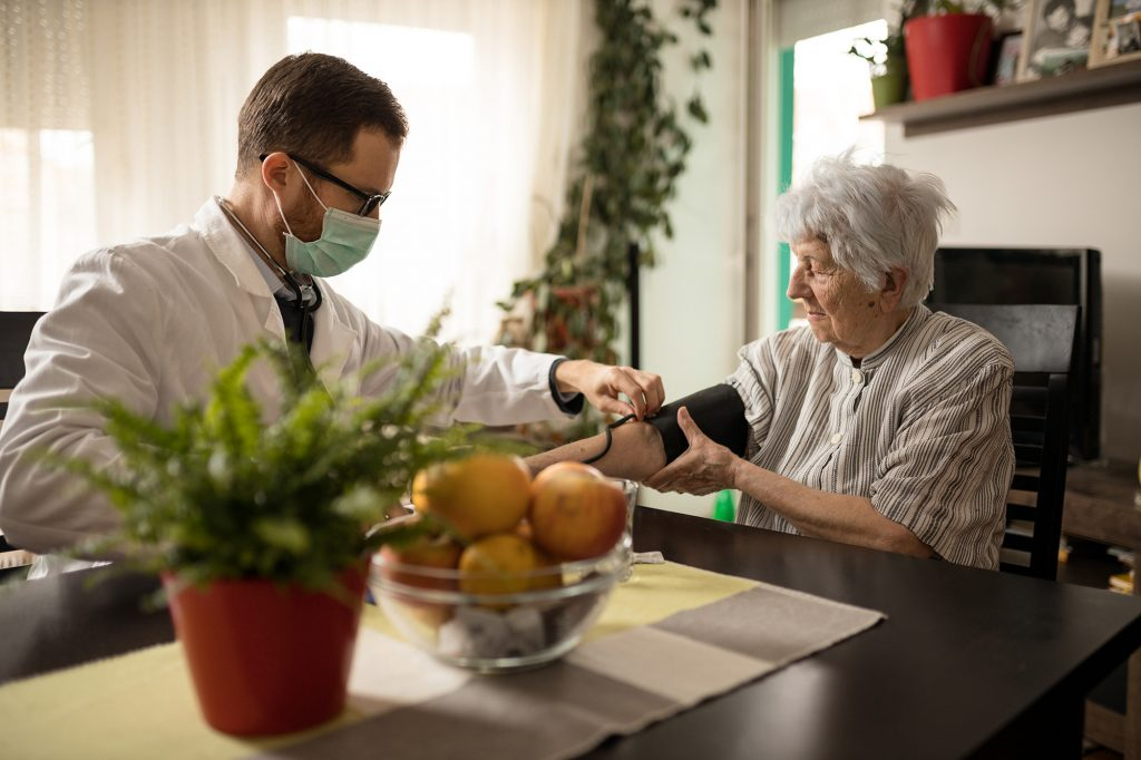 Doctor making a home-based primary care visit house call to an elderly patient