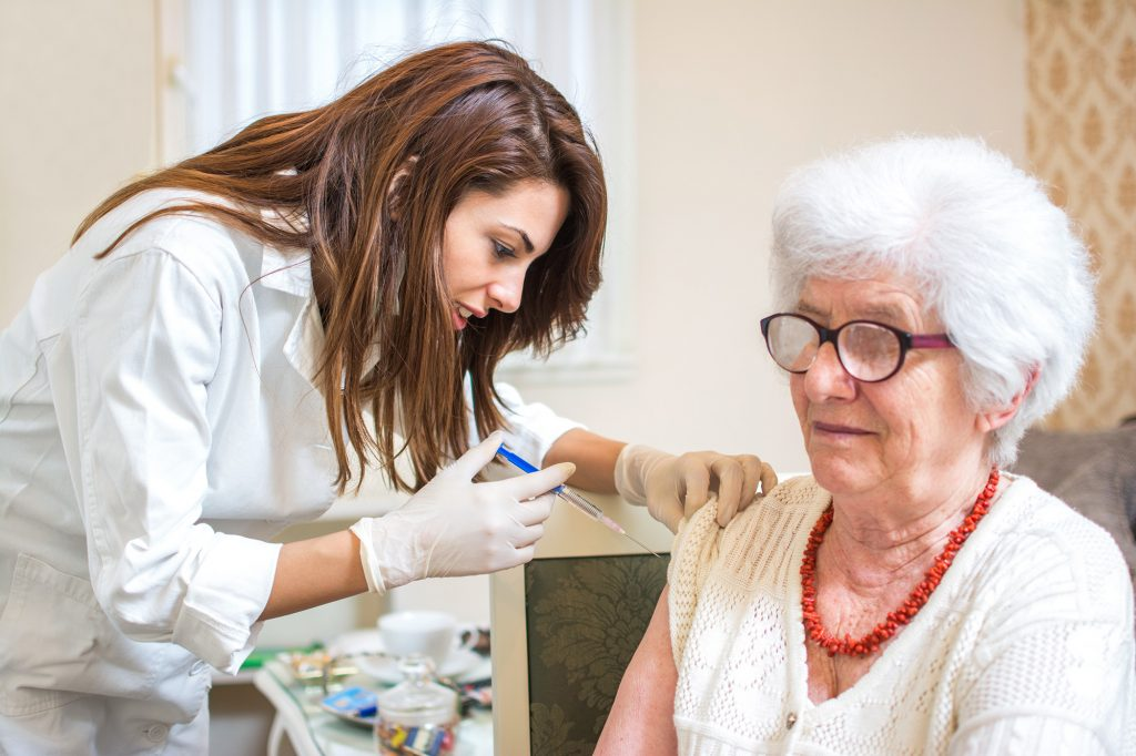 Elderly woman receiving Covid vaccine at home